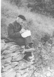 Professor J.C. Bradley sitting on a stone wall and taking notes while smiling