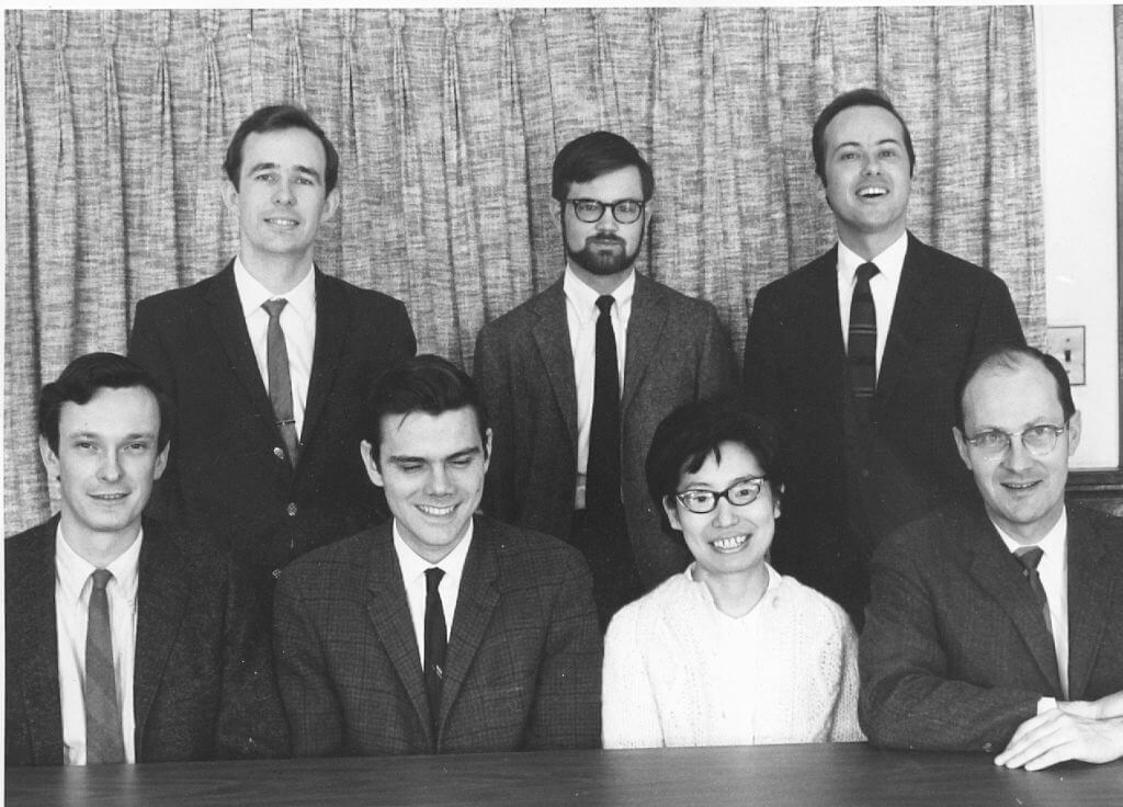 1969 Systematists posed for a group photo at a table in front of a curtain