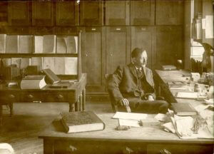 A.D. Mac Gillivray at a desk in White Hall